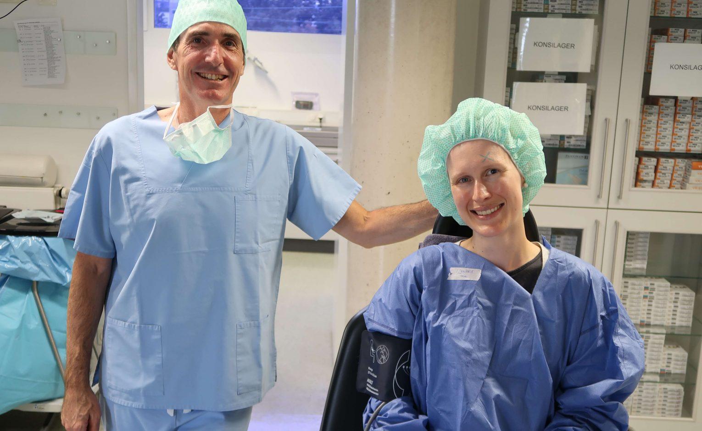 Augenarzt mit Patientin in OP-Kleidung